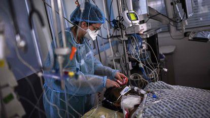 Enfermeira atende doente de coronavírus na UTI do hospital Cochin, em Paris, na quinta-feira.