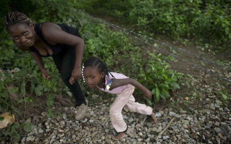 Uma imigrante hondurenha e sua filha tentam alcançar o trem em Chiapas, México.