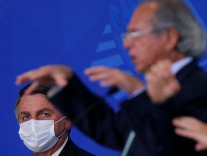 O presidente Jair Bolsonaro observa o ministro Paulo Guedes durante uma cerimônia em Brasília no último dia 19.