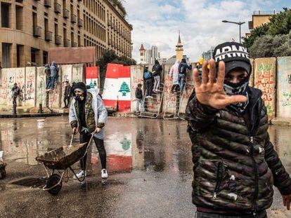 Vários manifestantes tentam atravessar as barreiras de concreto erguidas em 11 de fevereiro para impedir que civis entrem no Parlamento libanês, em Beirute.