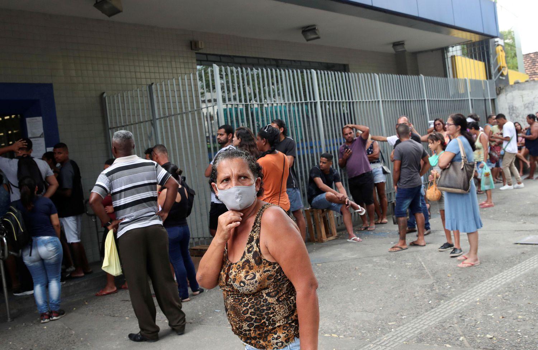 Dezenas de pessoas fazem fila em frente a uma unidade da Caixa, nesta quarta-feira no Rio de Janeiro, para tentar receber o auxílio emergencial anunciado pelo Governo.