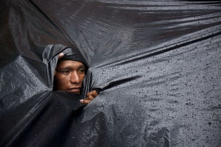 Um indígena mbyá guarani se protege da chuva.