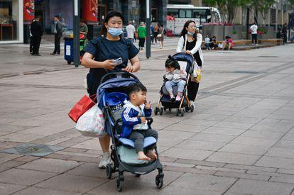 Mulheres com seus filhos em uma rua de Pequim em 31 de maio.