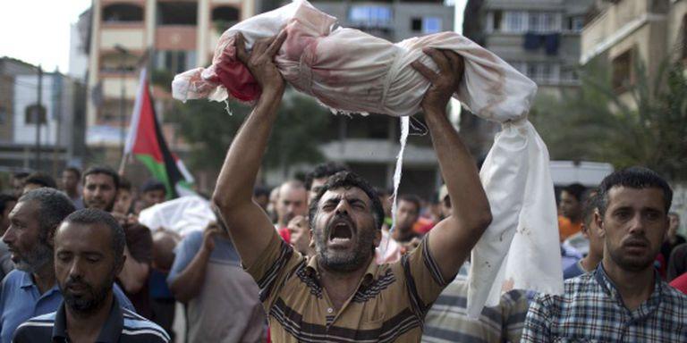 Um homem levanta o corpo de um menino de um ano, morto na quinta-feira no ataque a uma escola da ONU em Gaza.