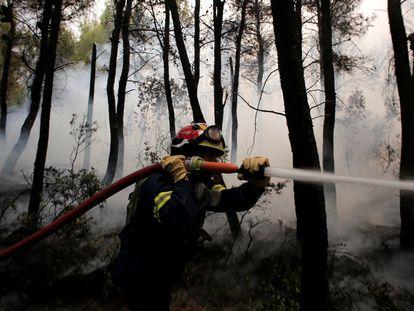 Um bombeiro luta contra o fogo na região de Kryoneri, ao norte de Atenas, na quinta-feira passada.