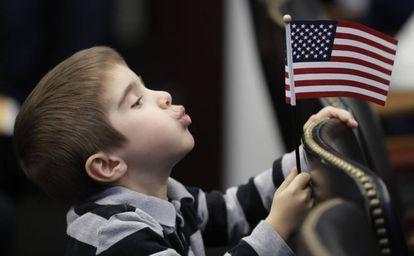 Menino brinca com bandeira dos EUA durante cerimônia de naturalização da mãe.