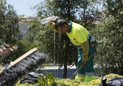 Jardineiro de Madri se refresca durante uma onda de calor de verão.