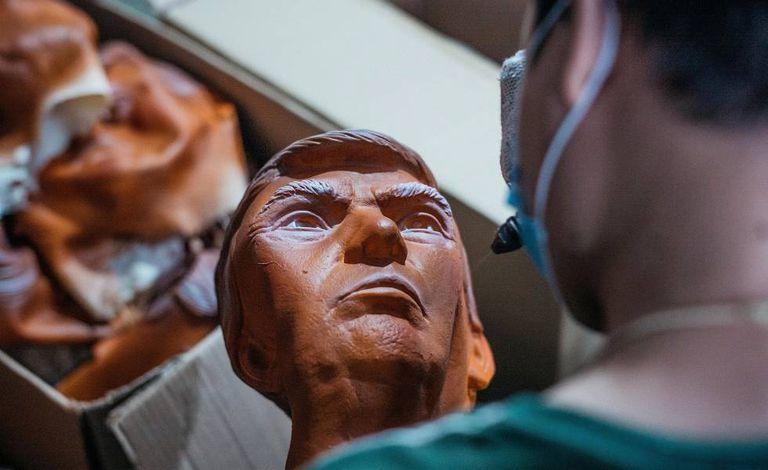 Operário pinta máscara de Trump em fábrica na China.