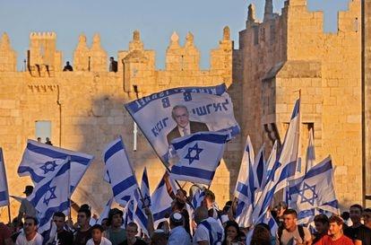 Israelenses hasteiam bandeiras do lado de fora da Porta de Damasco na Cidade Velha de Jerusalém, em 15 de junho de 2021, comemorando o aniversário da ocupação israelense de 1967 de Jerusalém Oriental.