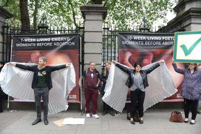 Ativistas pelo 'sim' tentam tampar cartazes contra o aborto em Dublin.