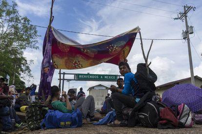 Migrantes centro-americanos diante da fronteira de El Ceibo.