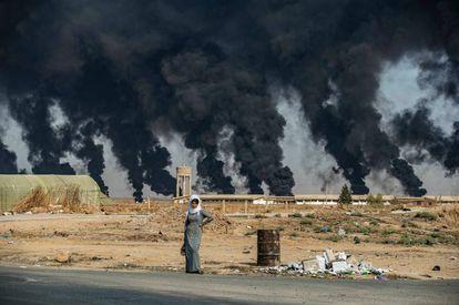 Uma mulher na frente da fumaça de pneus queimados pelos curdos para dificultar a visibilidade da aviação turca.