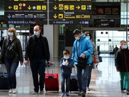 Crianças usam máscaras de proteção no aeroporto de Barcelona.