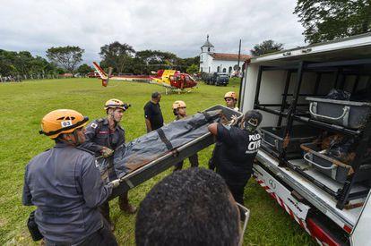 Bombeiros carregam um corpo recuperado em meio aos rejeitos em Brumadinho, no dia 28 de janeiro.