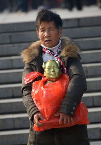 Uma anciã, com una estátua de Mao em bronze.