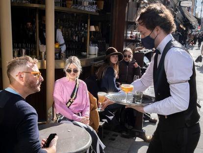 Um garçom atende clientes em um bar de Londres, em 12 de abril.