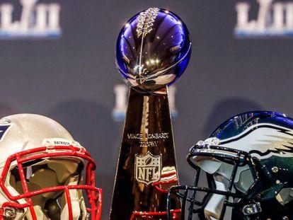 O capacete branco dos Patriots e o capacete verde dos Eagles ao lado do troféu Vince Lombardi.