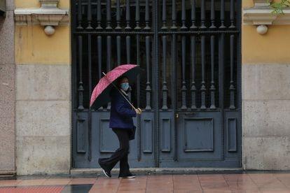 Mulher passa em frente a portão.