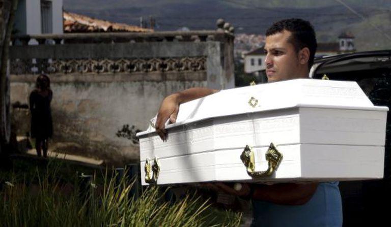 Homem carrega caixão de Emanuele, 5, vítima da tragédia.