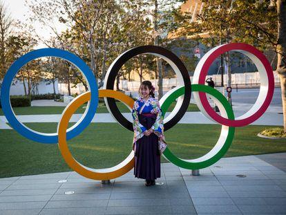 Japonesa vestida com um quimono diante dos anéis olímpicos de Tóquio