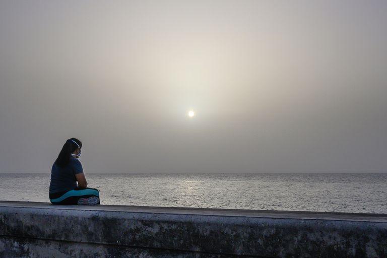 Uma mulher contempla a tempestade de areia do Saara na orla marítima de Havana, Cuba.