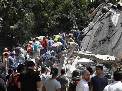 Pessoas buscam feridos debaixo de destroços em edifício derrubado por terremoto na cidade do México.