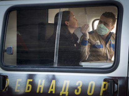 Um funcionário do Serviço Federal Russo de Vigilância coleta amostras para testar o coronavírus na estação de triagem especial ao ar livre no aeroporto de São Petersburgo, em 20 de março.