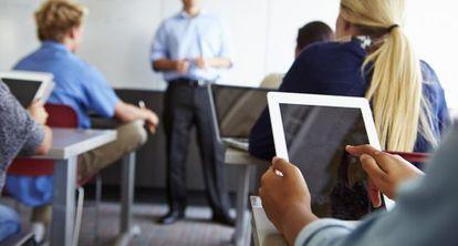 Estudantes usam um tablet em sala de aula.
