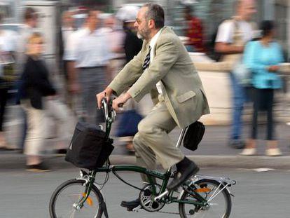 Um homem anda de bicicleta em Paris (França).