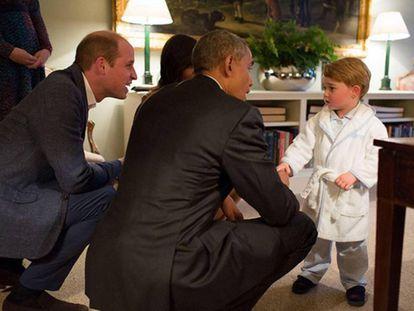 O príncipe George, de roupão, cumprimenta o presidente Obama.
