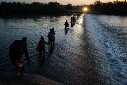 Um grupo de migrantes haitianos atravessa o rio Grande para obter alimentos e suprimentos perto do passo fronteiriço Del Río-Acuña, em Ciudad Acuña, Estado de Coahuila, México.