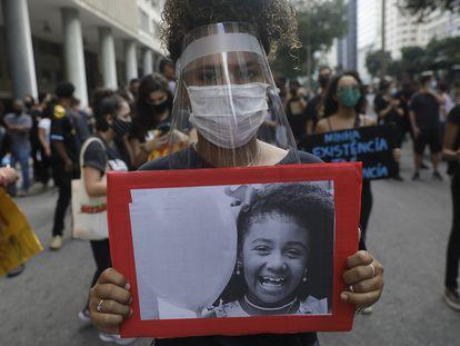 Mulher empunha foto de Ágatha, morta aos 8 anos durante uma ação policial no Rio de Janeiro em 2019.