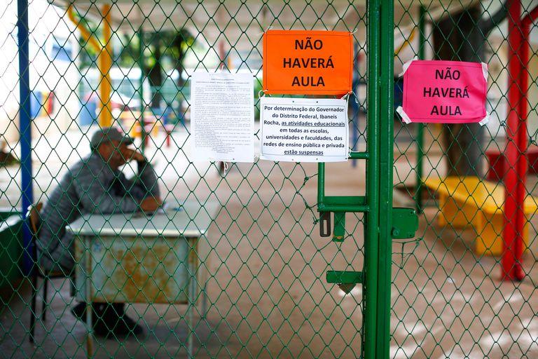 Um guarda permanece na entrada de uma escola pública em Brasília, que foi fechada para impedir o avanço do novo coronavírus, em 12 de março.