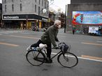 A man wears a face mask amid the ongoing COVID-19 coronavirus outbreak as he cycles on a quiet street in Beijing on March 26, 2020. (Photo by GREG BAKER / AFP)