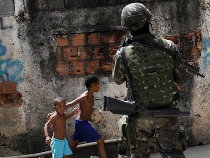 Crianças observam patrulhas das forças armadas durante uma operação contra traficantes no complexo de favelas de Lins, no Rio de Janeiro.