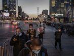 Ciudadanos chinos, todos ellos con mascarilla, hacen cola para coger el autobús el pasado 20 de marzo en Pekín.