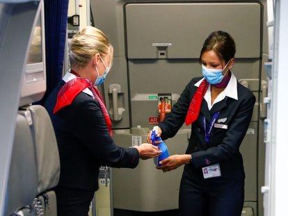 Aeromoços higienizam as mãos no aeroporto de Bruxelas, na Bélgica.
