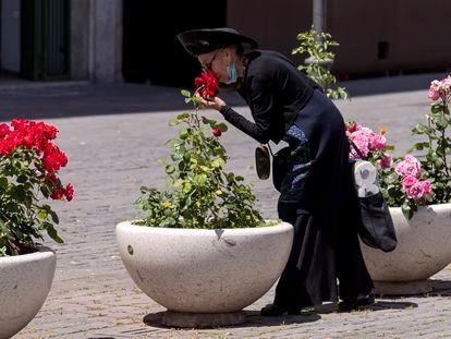 Uma mulher baixa a máscara para cheirar rosas em Roma, em maio passado, em pleno confinamento.