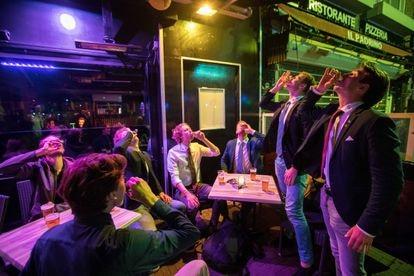 Grupo de jovens consome várias bebidas alcoólicas após a abertura dos bares na Holanda, há duas semanas.