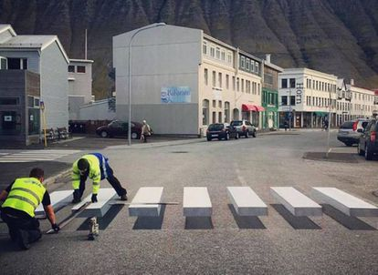 Dois operários pintam a faixa tridimensional em Ísafjörður (Islândia).