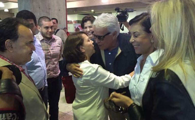 Mulher do opositor abraça Felipe González no aeroporto.