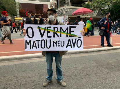 Clayton, que perdeu seu avô, exibe cartaz em protesto na avenida Paulista.