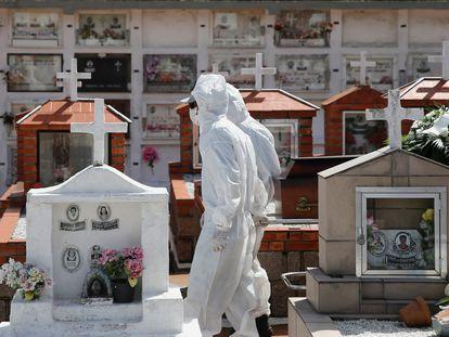 Trabalhadores puxam o caixão durante o sepultamento de uma vítima da covid-19, em um cemitério de Porto Alegre.