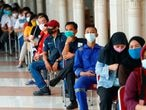 People wearing protective masks sit as they queue before receiving a dose of China's Sinovac Biotech vaccine for the coronavirus disease (COVID-19) at the Tanah Abang textile market, as Indonesia drives mass vaccination for vendors in Jakarta, Indonesia, February 17, 2021. REUTERS/Ajeng Dinar Ulfiana