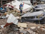 A firefighter inspects a destroyed car amid debris and damaged houses hit by the floods in Schuld near Bad Neuenahr, western Germany, on July 15, 2021. - Heavy rains and floods lashing western Europe have killed at least 45 people in Germany and left around 50 missing, as rising waters led several houses to collapse. (Photo by Bernd Lauter / AFP)