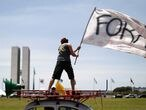 """A demonstrator waves a flag reading """"out"""" during a protest against Brazil's President Jair Bolsonaro and his handling of the coronavirus disease (COVID-19) crisis, in Brasilia, Brazil, January 31, 2021. REUTERS/Ueslei Marcelino"""