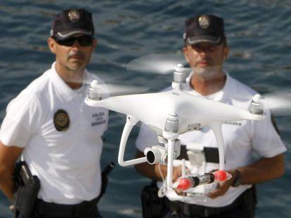 Agentes da polícia local de Benidorm e o drone usado para monitorar o litoral.