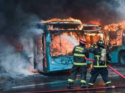 Bombeiros combatem incêndio em ônibus que foram atacados durante os protestos em Santiago.