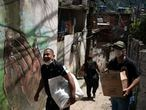 Volunteers carry packages with soap and detergent to be distributed in an effort to avoid the spread of the new coronavirus in the Rocinha slum in Rio de Janeiro, Brazil, Tuesday, March 24, 2020. (AP Photo/Leo Correa)