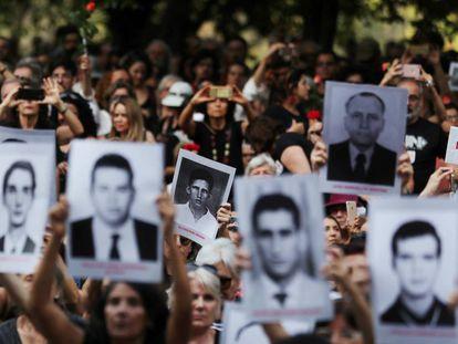 Manifestantes mostram placas com fotos de vítimas da ditadura durante protesto em julho de 2019.